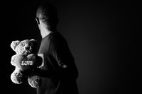 Sad young African man with teddy bear and love sign text in black and white