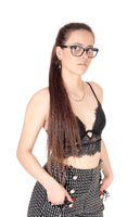 Serious looking woman standing in profile is shorts and bra with glasses