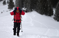 Hiker with hands on head at off-piste snowy slope in snow-covered forest