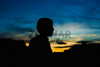 Dark backlit silhouette of a happy and smiling child at dusk, with a background of intense blue and orange sky.