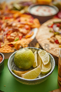 Close up on lime slices in ceramic bowl with various freshly made Mexican foods