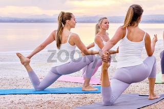 Women practising yoga do One-Legged King Pigeon Pose Eka Pada Rajakapotasana