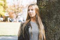 dreamy teenage girl leaning against tree