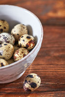 Ceramic white bowl with quail eggs on a brown wooden table with copy space. Top view