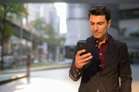 Young handsome Hispanic businessman using phone outside the office building