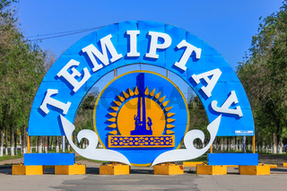 Detail View of the colorful Emblem and Flag of City Temirtau on the End of the main Promenade. Outgoing Street with many Threes to Karaganda Region. Kazakhstan. Symbol with Monument of Metallurgists.