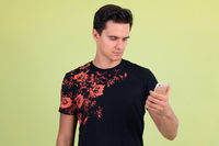 Portrait of young handsome man using phone