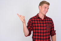 Happy young handsome hipster man with blond hair pointing finger