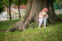Girl sitting under a tree holding teddy bear