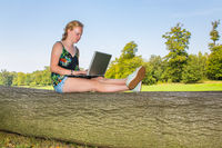 Woman on tree trunk works on laptop