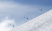Snowy off-piste ski slope with traces from skis and snowboards and chair-lift