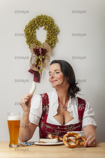 Bayerische Frau in einem Dirndl beim  Essen