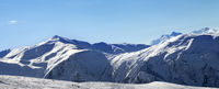 Panoramic view on snowy ski slope in sunny morning