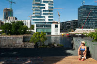 Berlin, Germany, A woman sunbathes at the banks of the Spree River in Friedrichshain