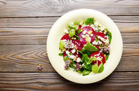 Top view at mediterranean roasted beet salad with walnuts feta cheese oregano and mash leaves on wooden table