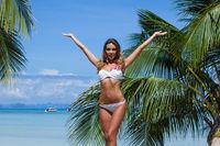 Woman in bikini raising arms beach