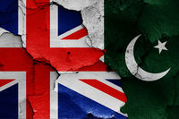 flags of UK and Pakistan painted on cracked wall
