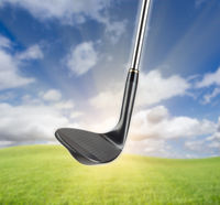 Black Golf Club Wedge Iron Against Grass and Blue Sky Background