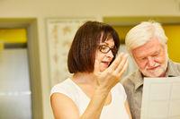 Ärztin zeigt Senior Mann den Behandlungsplan