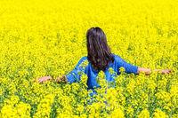 Woman walks in flourishing yellow rapeseed field