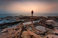 Woman standing on sandstone rocks with foggy coastal sunrise
