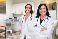 Hispanic and Caucasian Female Doctors Standing In Office