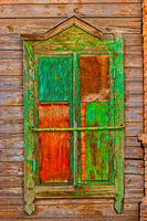 Shabby window of old wooden house painted in green and red