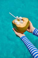 Coconut in hands over against turquoise sea