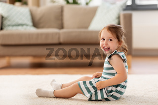 happy baby girl sitting on floor at home