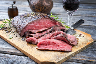Traditional barbecue dry aged sliced roast beef steak with herbs as closeup on an old cutting board