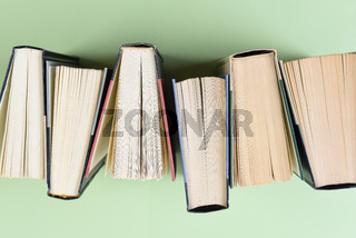 High angle closeup of a row of books on a light green background