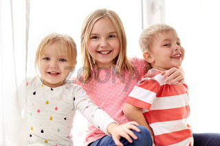 happy little kids hugging at window