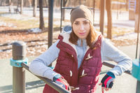 Portrait of a girl athlete in a hat with gloves and a warm vest next to a workout playground outdoors in the winter on a sunny day