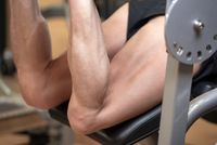 Man flexing isquiotiobial leg muscles on leg curl gym machine. Sport, fitness, bodybuilding and people concept.