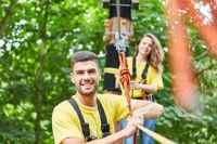 Mann im Hochseilgarten mit Seil gesichert