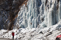 Man in red down jacket makes photo of icy mountain waterfall