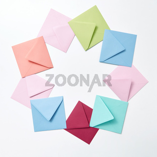 Round frame of colored craft blank envelopes on a light background.