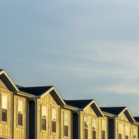 Square Townhouses on a neighborhood under blue sky and clouds on a sunny day