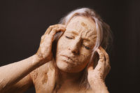 woman covered in dry cracked clay mud mask holding her head