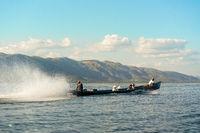 Burmese locals use powerful long boat to cross Inle Lake, Myanmar.
