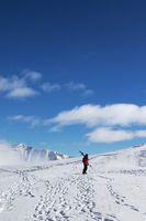 Skier with skis on his shoulder and snowy mountain