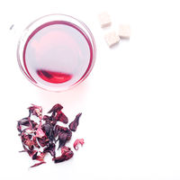 Top view of Hibiscus Tea cup with petals and sugar cubes aside on white background
