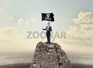 Businessman on the top of a rock holding pirate flag