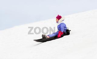 happy little girl sliding down on sled in winter