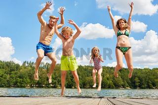 Familie am Badesee macht einen Luftsprung