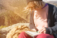 Portrait of a hipster girl wearing sunglasses and a hat sitting on a rock outdoor in the mountains against a blue sky. Freelancer designer in travel draws crayons pastels in a notebook