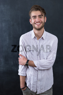 Handsome young student in shirt standing against blackboard