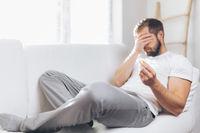 Heartbroken man at home holding a wedding ring
