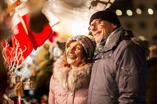 senior couple at christmas market souvenir shop