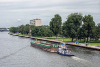 Tugboat with cargo at Dutch Amsterdam-Rijn canal near city Utrecht